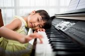 image of modifier  - Little Vietnamese girl playing synthesizer and lookingat the camera buttons are digitally modified - JPG