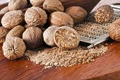 stock photo of ground nut  - Ground nutmeg on wooden table background - JPG