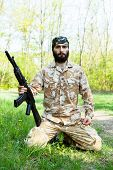 stock photo of rifle  - Bearded soldier with a rifle in the woods - JPG