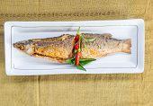 stock photo of mullet  - fried mullet fish and herb on white plate - JPG