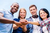 picture of bonding  - Low angle view of four happy young people bonding and holding hands clasped with blue sky in the background - JPG
