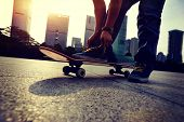 foto of skate board  - young woman skateboarder tying shoelace at skate park - JPG