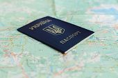 foto of passport cover  - an image of Ukrainian passport on a the background of the tourist map - JPG