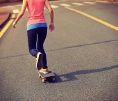 picture of skateboard  - one young woman skateboarder skateboarding on road - JPG
