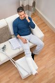 image of crutch  - High Angle View Of A Man With Crutches Sitting On Sofa Talking On Cellphone - JPG