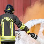 stock photo of fire brigade  - firefighters in action with foam to put out the fire of the car - JPG
