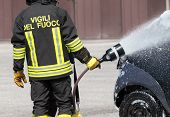stock photo of fire brigade  - firefighter in action with foam to put out the fire of the ca - JPG