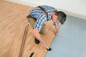 image of angle  - High Angle View Of A Worker Assembling New Laminate Floor - JPG