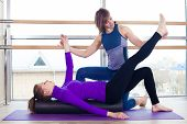 picture of pilates  - Aerobics Pilates personal trainer helping women group in a gym class - JPG