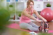 stock photo of stretch  - Stretched young pretty woman sitting on exercising mat - JPG
