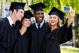 stock photo of graduation gown  - Four college graduates in graduation gowns standing close to each other and making selfie - JPG