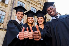 foto of graduation gown  - Low angle view of four college graduates in graduation gowns standing close to each other and showing their thumbs up - JPG