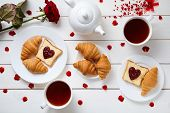 Постер, плакат: Romantic breakfast for Valentines day with toasts heart shaped jam croissants rose petals and tea