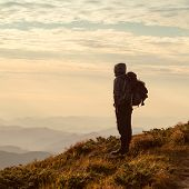 Постер, плакат: Traveler with backpack and mountain panorama