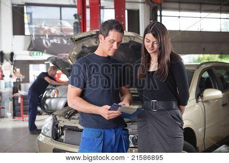 Постер, плакат: Механик показываю стоимость услуги женщин клиенту во время человек работающий в фоновом режиме, холст на подрамнике