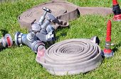 stock photo of hookup  - valves and fire hoses before the event on grass - JPG