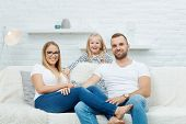 Family portrait. Happy family sitting on couch and having fun at home, smiling. Family with one chil poster