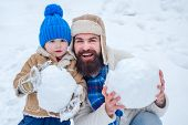 Happy Father And Son Making Snowman In The Snow. Handmade Funny Snow Man. Father And Son Making Snow poster