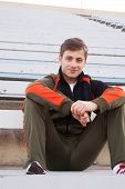 picture of bleachers  - handsome male athlete sitting in the bleachers - JPG