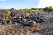 Old Black Rubber Tires Discarded On The Dry Ground With Tire Tracks poster