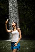 Happy Caucasian Woman Enjoying Waterfall Landscape In Tropic, Taking Selfie With Smartphone Near Wat poster