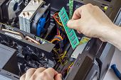Professional Man Are Repairing And Assembling A Computer Inside. Male Hand Inserts A Motherboard Int poster
