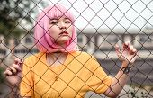 Stylish Asian Teenager In Pink Wig And Modern Street Outfit Looking At Camera While Standing Behind  poster