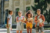 Four Adorable Multicultural Schoolchildren Standing In Schoolyard And Holding Books poster