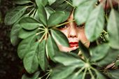 A close up portrait of a lovely mysterious girl with green leaves. Beauty, cosmetics. poster