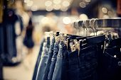 Jeans On The Hanger In The Store. Clothes On Hangers In Shop For Sale. Blur Background. Fashionable  poster