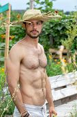 Handsome Hairy Shirtless Man With Straw Hat Standing In Garden poster