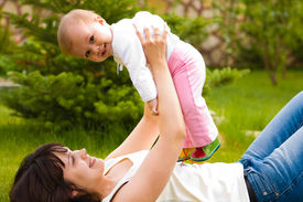 stock photo of mother baby nature  - Mother and child outdoors together and happy - JPG