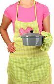 foto of homemaker  - Closeup of  homemaker in apron  holding  pan isolated on white - JPG
