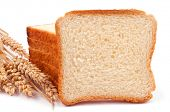 A heap of bread slices and one slice like a copy space, leaning on the heap and wheat ears - isolat