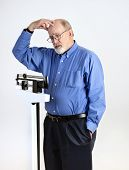 Senior Man On Weight Scale Looking Worried And Confused, Holding Head