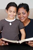 stock photo of girl reading book  - Minority woman and her daughter reading the Bible - JPG