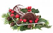 stock photo of yule  - Christmas chocolate yule log cake with red baubles and holly over white background - JPG