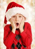 7 years old surprised boy in Santa hat Christmas portrait on lights background