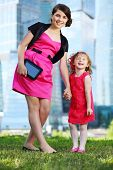 pic of bolero  - Beautiful girl with tablet pc and little laughing girl stand near blue skyscrapers - JPG