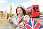 London tourist woman holding shopping bag near showing thumbs up sign happy excited near Big Ben. Sh