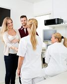 pic of gynecologist  - Young expectant couple visiting gynecologist at clinic - JPG