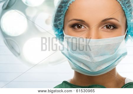 Young woman doctor in cap and face mask in surgery room interior poster