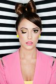 Portrait of beautiful young winking woman with professional party make up false eyelashes on stripy