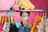picture of annoying  - Time for refreshing wardrobe young attractive surprised woman searching for clothing in a closet  - JPG
