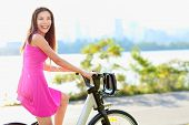 stock photo of exercise bike  - Woman biking in city park on bicycle - JPG