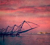 Vintage retro hipster style travel image of Kochi chinese fishnets on sunset. Fort Kochin, Kochi, Ke
