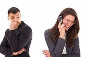 stock photo of envy  - suspicious man looking at his woman talking on the phone smiling