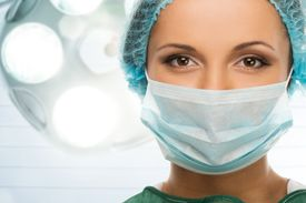 stock photo of face mask  - Young woman doctor in cap and face mask in surgery room interior - JPG