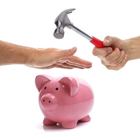 image of raid  - Hand with hammer about to smash piggy bank to get at savings being protected by another hand concept for protecting your assets - JPG