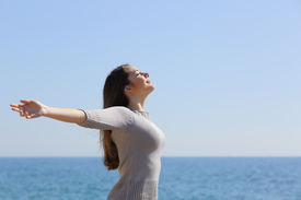image of breathing exercise  - Happy relaxed woman breathing deep fresh air and raising arms on the beach with the horizon in the background - JPG
